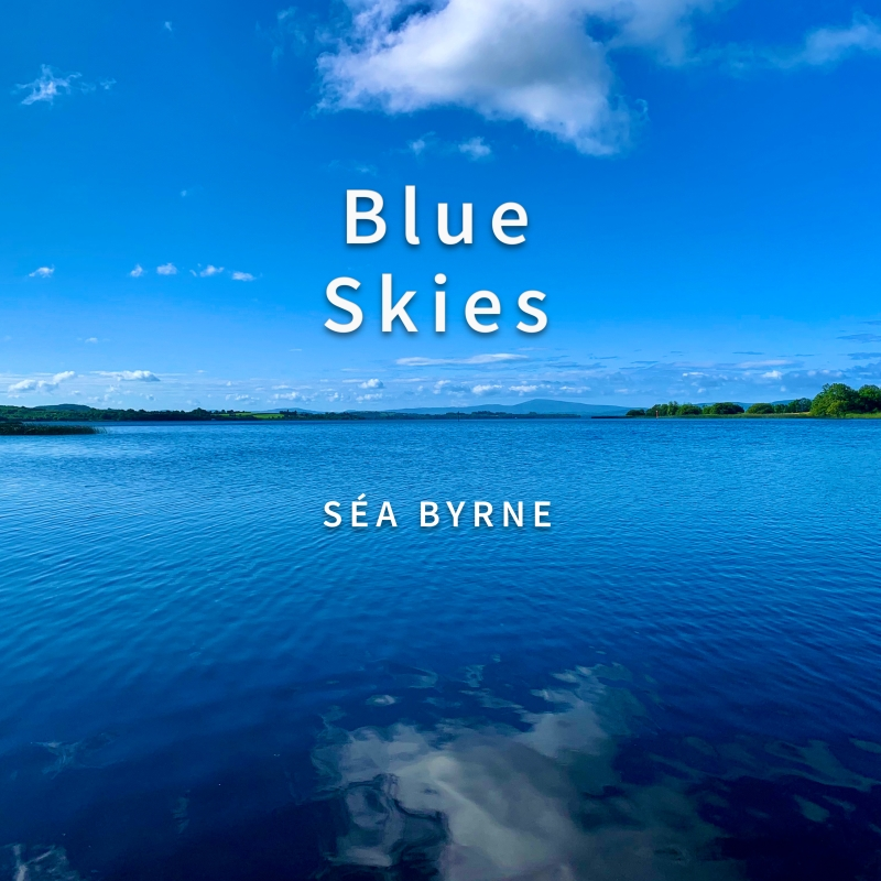 """A shot looking across Lough Derg with sky and water. Mostly blue skies with some clouds reflected upon the surface of the lake. """"Blue Skies"""" and """"Séa Byrne"""" text overlaid above the photograph."""
